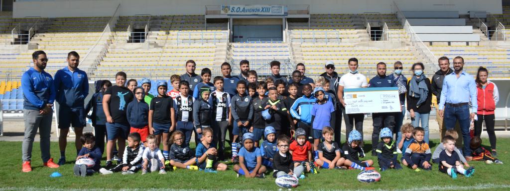 Les enfants de l'école de Rugby posent avec le chèque remis par la Fondation Vinci